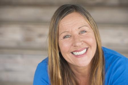 Retrato atractiva mujer madura con expresión de confianza relajado feliz, sonriente amable, fondo borroso, copia espacio. Foto de archivo - 39418579