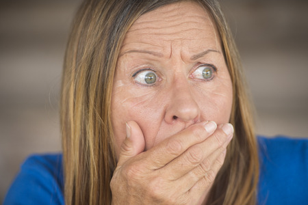 facial expressions: Portrait attractive mature woman with shocked, anxious, fearful facial expression, covering mouth with hand, blurred background. Stock Photo