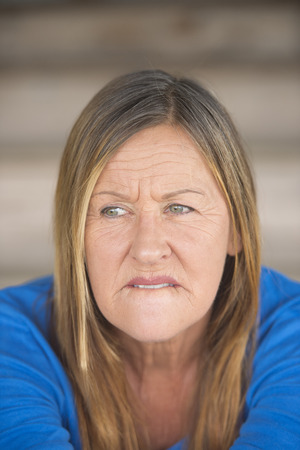 hesitant: Portrait attractive mature woman with worried nervous thoughtful angry expression, , blurred background.