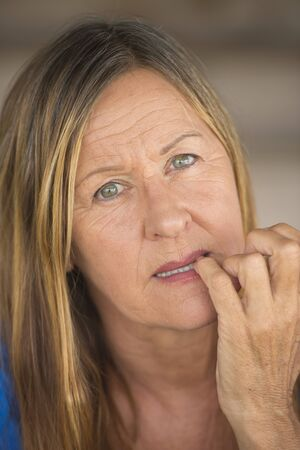 insecure: Portrait attractive mature woman with nervous stressed hesitant facial expression, biting insecure finger nails, blurred background. Stock Photo