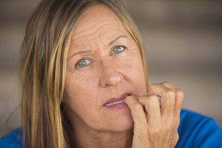 insecure: Portrait attractive mature woman with nervous stressed insecure facial expression, biting finger nails, blurred background. Stock Photo