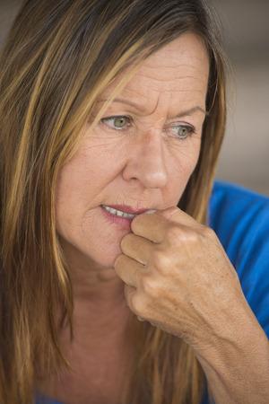 mujer sola: Retrato atractiva mujer madura con inseguridad nervioso destac� la expresi�n facial, u�as morder, fondo borroso.
