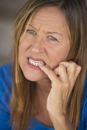 hesitant: Portrait attractive mature woman with nervous hesitant stressed facial expression, biting finger nails, blurred background.