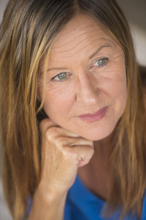 Portrait attractive mature woman with thoughtful serious facial expression, relaxed, peaceful daydreaming, blurred background.