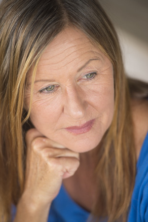 laid back: Portrait attractive mature woman with thoughtful lonely facial expression, relaxed, peaceful daydreaming, blurred background.