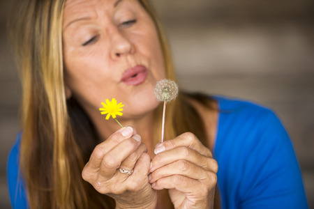 laid back: Portrait of attractive mature woman in blurred background blowing dandelion flower, happy relaxed, friendly, copy space.