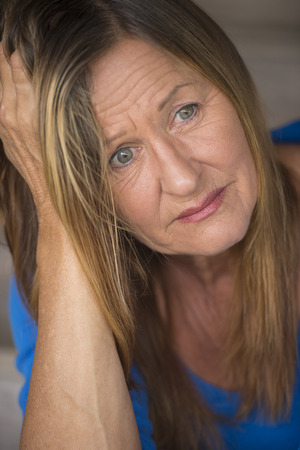 Portrait attractive mature woman with sad, depressed and stressed facial expression, worried, blurred background. Stock Photo