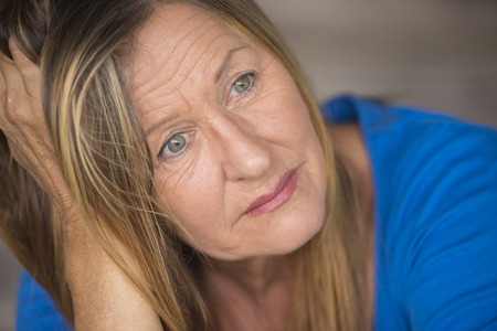 senior depression: Portrait attractive mature woman with sad, lonely, depressed and stressed facial expression, worried, blurred background.