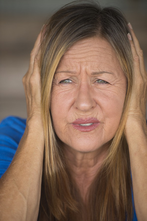 hands covering ears: Portrait attractive mature woman with stressed, painful facial expression, hands covering ears from loud noise and sound, blurred background.