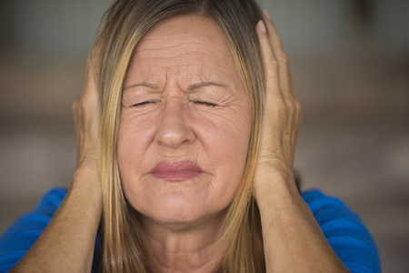 hands covering ears: Portrait attractive mature woman with stressed, painful facial expression, with closed eyes, hands covering ears from noise, blurred background. Stock Photo