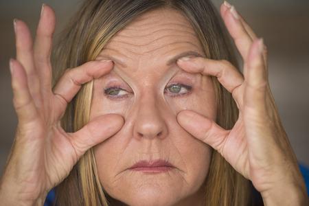 insomnio: Retrato de la atractiva mujer madura con la expresión facial cansado y estresado, dedos mantener los ojos abiertos, insomnio y dolor de cabeza, fondo borroso. Foto de archivo