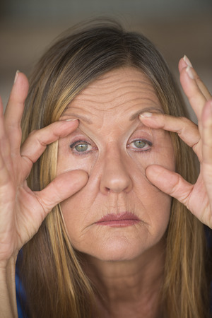 Portrait of attractive mature woman with tired and stressed facial expression, fingers keep eyes open, suffering pain and headache, blurred background.