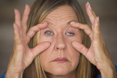 weary: Portrait of attractive mature woman with tired and stressed facial expression, fingers keep eyes open, suffering migraine and headache, blurred background. Stock Photo