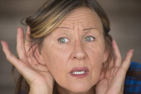 interested: Portrait attractive mature woman with hands at ears listening with curious, interested and anxious facial expression to loud noise or sound, blurred background. Stock Photo