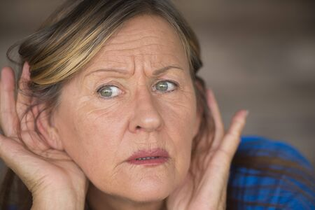 loud noise: Portrait attractive mature woman with hands at ears listening with curious and anxious facial expression to loud noise or sound, blurred background.