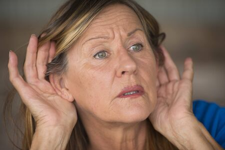 interested: Portrait attractive mature woman with hands at ears listening with curious, interested and surprised facial expression to loud noise or sound, blurred background. Stock Photo