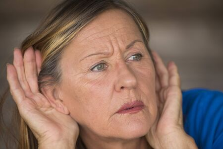 Portrait attractive mature woman with hands at ears listening with curious, interested and worried facial expression to loud noise or sound, blurred background. Stock Photo