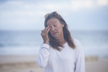 MENOPAUSE: Portrait attractive mature woman with closed eyes, stressed, tired, suffering from menopause, blurred background outdoor, copy space. Stock Photo
