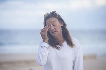 closed eyes: Portret van aantrekkelijke rijpe vrouw met gesloten ogen, gestrest, moe, die lijden aan de menopauze, onscherpe achtergrond outdoor, kopiëren ruimte.