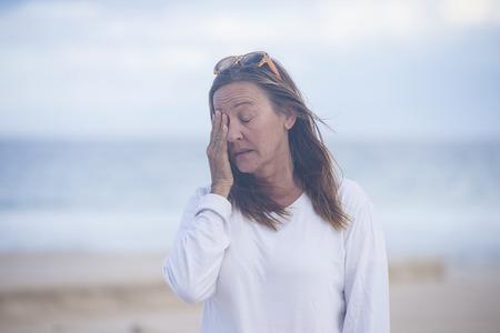 Portret atrakcyjne starsze kobiety z zamkniętymi oczami, zestresowany, zmęczony, smutny, cierpi z powodu menopauzy, niewyraźne tło na zewnątrz, miejsca kopiowania.