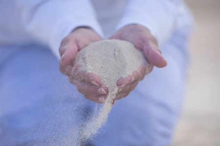 seeping: Fine mineral sand seeping through finger of two hands at windy beach, blurred background and copy space.