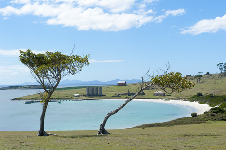 Bay on Maria Island, Tasmania, Australia, with ruins of old Darlington Convict Settlement, World Heritage Site and National Park, with mountains of Freycinet Peninsula in background. photo