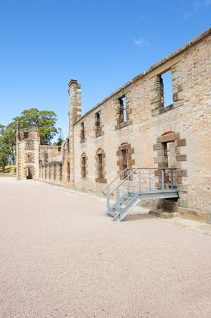 gaol: World Heritage Site of  Port Arthur Convict Museum Settlement in Tasmania, Australia, with ruin of historic prison building, tourist destination, blue sky.