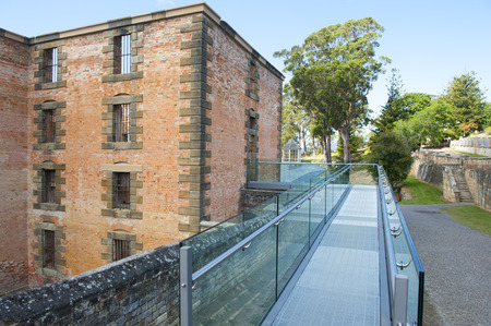 gangway: World Heritage Site of  Port Arthur Convict Museum Settlement in Tasmania, Australia, with ruin of historic prison building with modern gangway.