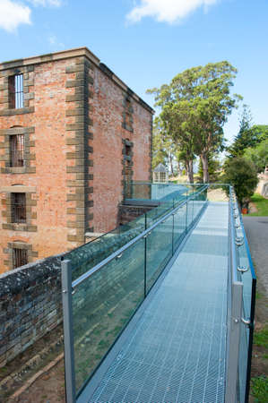 gaol: World Heritage Site of  Port Arthur Convict Museum Settlement in Tasmania, Australia, with ruin of historic prison building with new metal gangway.