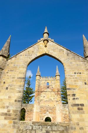 arthur: World Heritage Site of  Port Arthur Convict Museum Settlement in Tasmania, Australia, with ruins of historic church building, tourist attraction, blue sky.