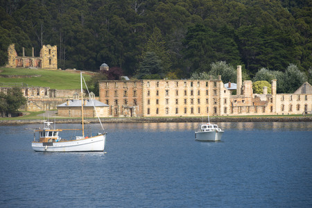 arthur: World Heritage Site of former Penal Convict Settlement Port Arthur on Tasmania, Australia, with ruin of prison at water of harbour and other old buildings.