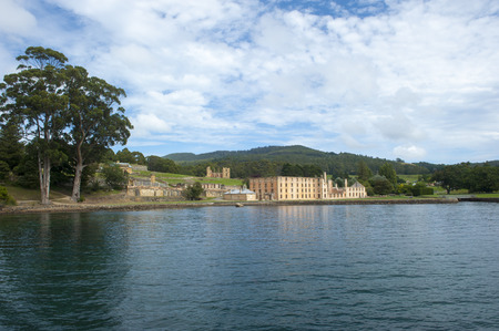 penal:  former Port Arthur Penal Settlement on Tasmania Australia with ruins and relicts of prison and other buildings with view over harbour with forest hills in blurred background and copy space.