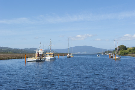 anchoring: Anchoring boats on the water of Huon River valley south of Hobart Tasmania Australia with shoreline and mountains in blurred background summer sunny blue sky as copy space.