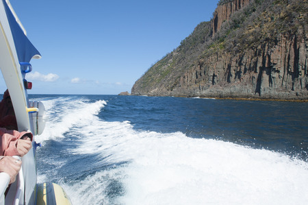 Tourist Boat trip along steep high rocky coast of Bruny Islans, Tasmania, with view over Southern Ocean to horizon, summer sunny blue sky and copy space. photo