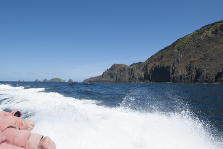 Sailing tour along steep high cliff coast of Bruny Island, Tasmania, with view over remote wild Southern Ocean to horizon, blue sky and copy space. photo