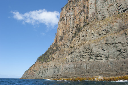 Steep high rocky cliff coast at Bruny Island, Tasmania, Australia, popular tourist destination, with view over Southern Ocean to horizon, summer blue sky as copy space. photo