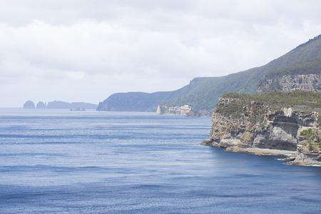 tasman: Wild steep cliffs along coastline in Tasmania, close to Port Arthur in Tasman Peninsula National Park, Australia, misty ocercast sky as blurred background and copy space. Stock Photo