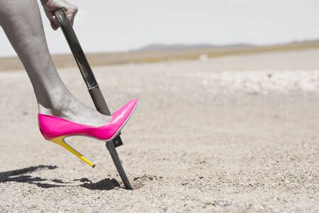 shovel in dirt: Concept filtered image of womans leg wearing pink high heel stiletto shoe and one hand on shovel, digging in remote sandy desert hole in the dirt