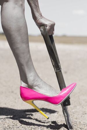 high desert: Concept filtered image of female leg wearing pink high heel stiletto shoe and one hand on shovel, digging in remote sandy desert hole in the dirt
