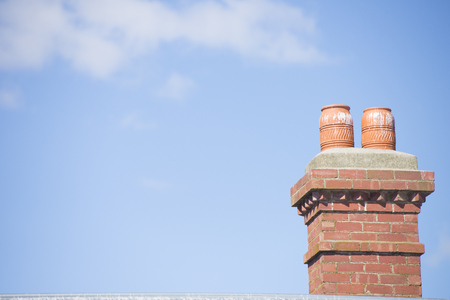 outdoor fireplace: Red brick chimney on top of roof of house with fireplace heating