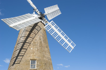 the 19th century: Heritage listed building of historic flour windmill with white wings at Oatlands, Tasmania, Australia, built in the 19th century, mill restored and still working, blue sky and copy space.