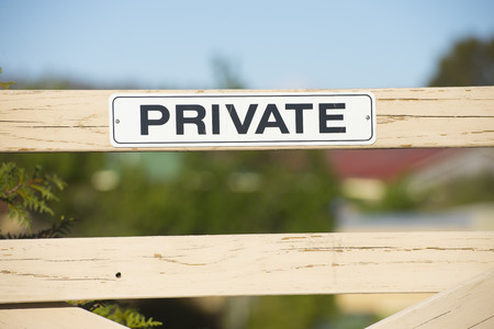 private access: Private property sign at wooden fence or gate signaling restricted access to land behind