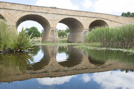 arcos de piedra: Edificio histórico en el patrimonio en la lista de Richmond, Tasmania, el más antiguo puente de piedra construido convicto en Australia, imagen de espejo con reflejo en el agua del río por debajo de los arcos