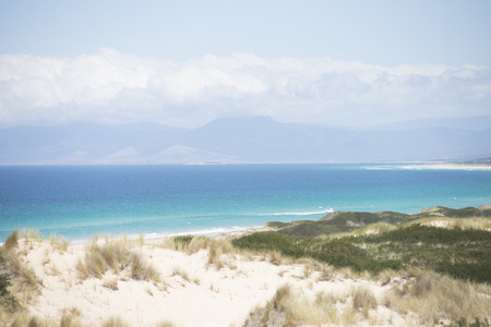 Coastline at Bay of Fires, Tasmania, Australia, at sunny summer day, with high sand dunes, turquoise ocean water, mountains as blurred background photo