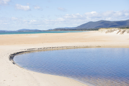 Remote beach at Chain of Lagoons, popular summer tourist destination at east coast of Tasmania, Australia, mountains in blurred background of turqoise ocean bay and sand dunes. photo