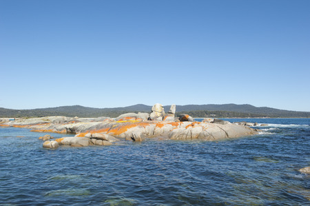 Orange coloured rocks along the coastline of the Bay of Fires, northeast Tasmania, with crystal clear ocean, mountains in hinterland, attractive tourist destination, copy space. photo