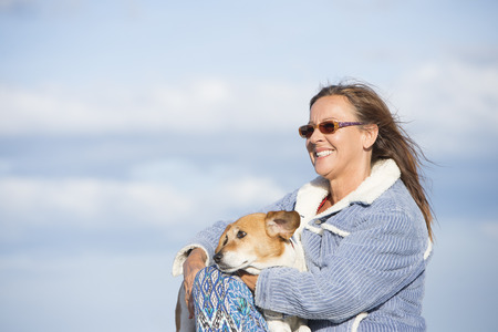 beautiful mature woman: Portrait of attractive mature woman sitting outdoor with pet dog friend relaxed on sunny day