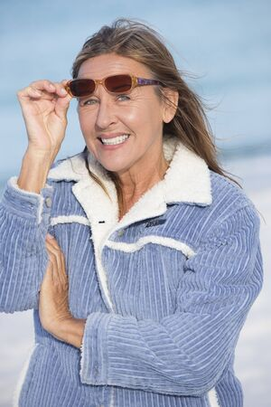 warm jacket: Portrait of beautiful mature woman posing happy confident and relaxed smiling outdoor in warm jacket and sunglasses in cold winter at ocean