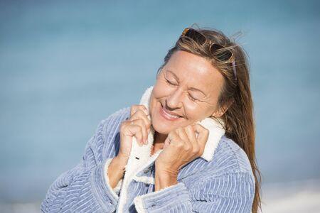 ojos cerrados: Retrato de mujer madura atractiva posando pensativa y feliz relajado sonriendo con los ojos cerrados al aire libre en la chaqueta cálida y gafas de sol en invierno frío en el océano