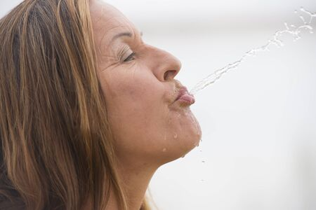 spewing: Portrait attractive mature woman spilling, spewing water into the air, with drops running down face